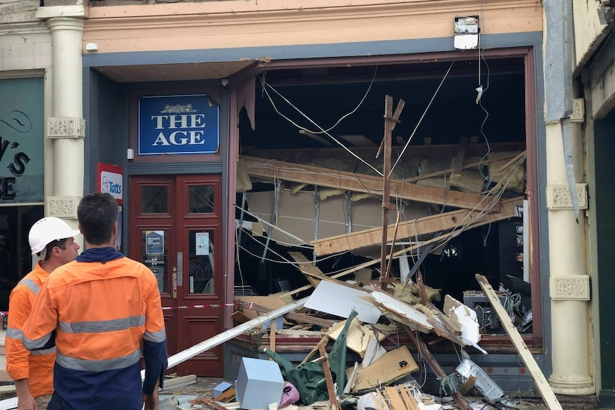A shopfront that has been smashed in by a piece of heavy machinery.