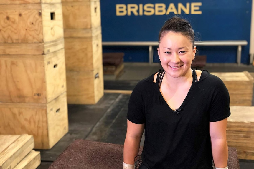Professional female weightlifter Erika Yamasaki smiles as she sits on a wooden box at the Cougars Weightlifting Club in Brisbane