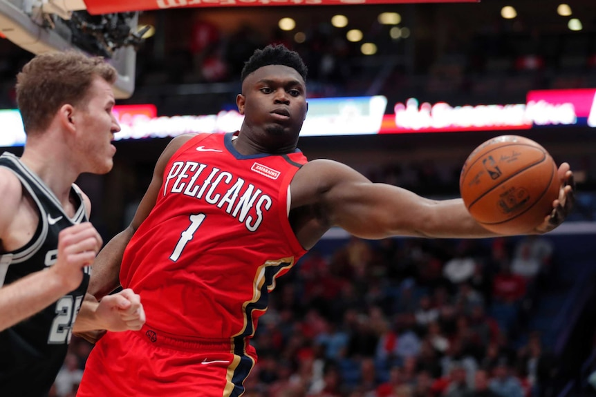 Zion Williamson reaches for the basketball in his NBA debut.