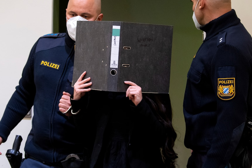 Woman in black escorted by two police in face masks covers face with black folder