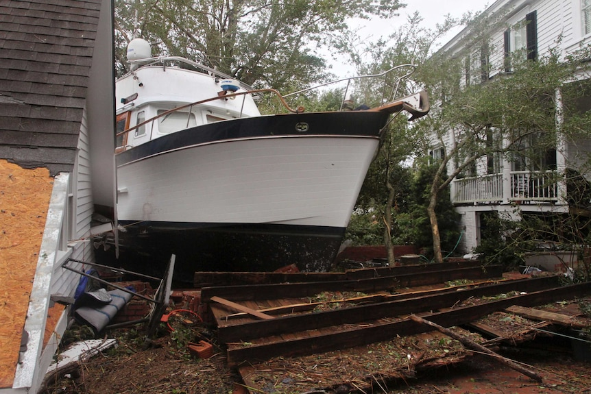 A boat rests between the shifted roof of a garage and a damaged home