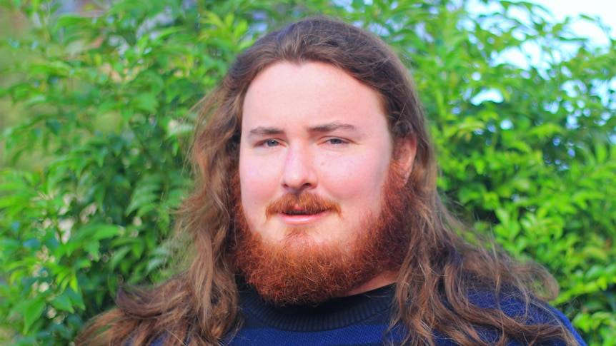 A man with a red beard and hair, in front of a green tree, with a blue jumper on. He is serious.