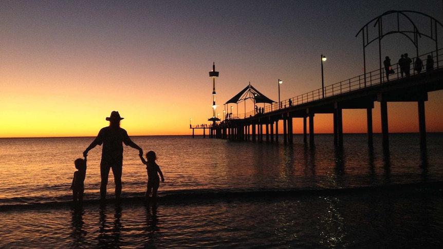 A family play in the shallows at Brighton Beach during sunset.