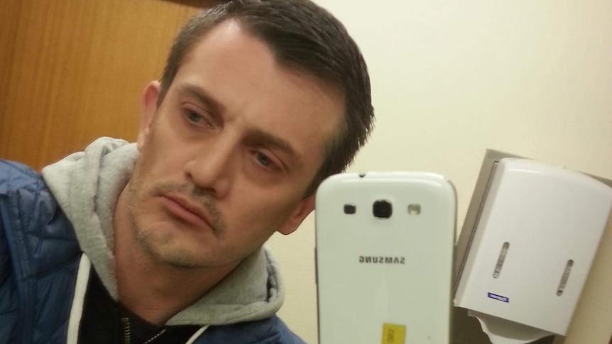 A man takes a selfie in a mirror.