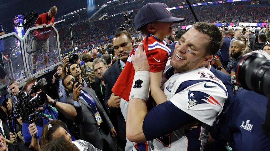 New England Patriots' Tom Brady lifts his son, Ben, after winning NFL Super Bowl LIII in Atlanta.