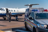 A police plane a police officer and an NT Police car on the runway.
