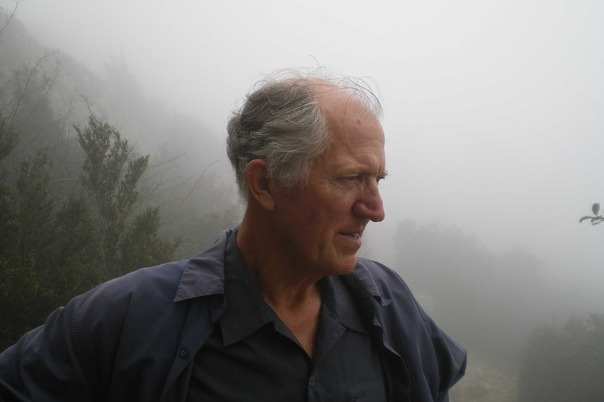 Clive Deverall stands on a mountain surrounded by white mist.