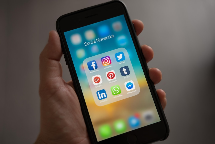 Social media icons on a phone screen. A hand is holding the phone but the person is out of frame.
