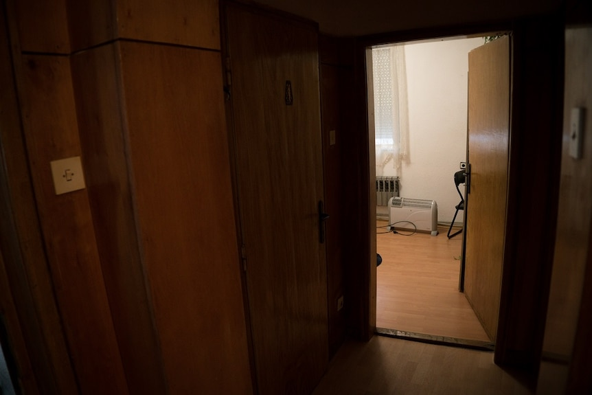 A heater and a chair can be seen through the open door of room