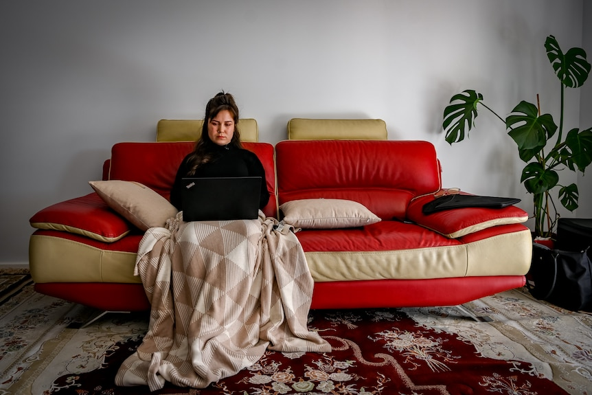 A woman sitting on the couch, using her laptop.