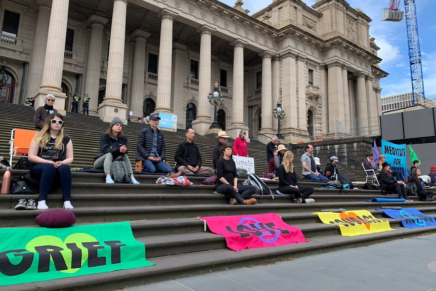 Climate activists sit peacefully on the steps of the Victorian Parliament.