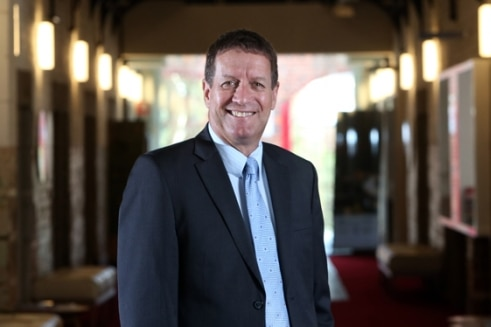 Dale Pearce smiles, wearing a suit.