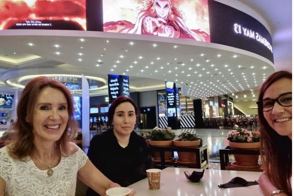 Three women sit at a table at a brightly lit mall with a restaurant in the background.