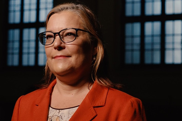 A woman wears glasses and an orange jacket.