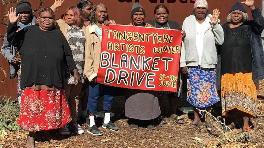 Woman stand in front of a banner promoting blanket drive