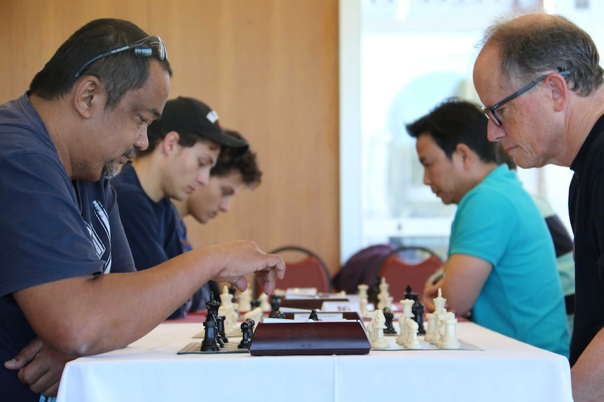 Chess player in the foreground about to make his move.