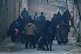 People carry belongings as they flee down a street.