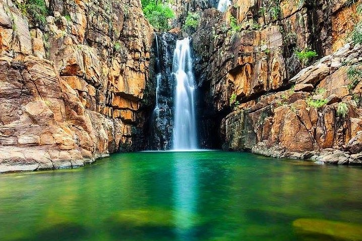 A waterfall falls into the Southern Rockhole at Nitmiluk, Northern Territory