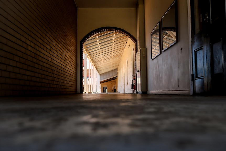 An indoor corridor with a brick wall on one side and a wooden door on the other looking toward an outside walkway