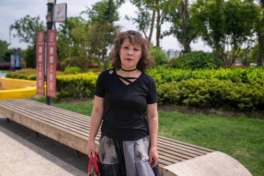 A middle aged woman stands in a Shanghai park.
