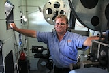 Steve Snell with two old film projectors