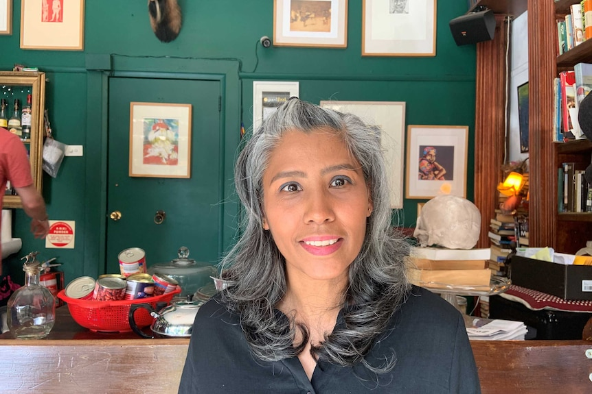 A woman sits in a room with a green wall covered in framed artworks and a bookshelf