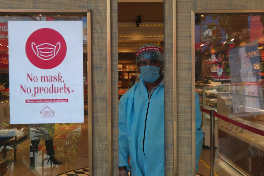 An Indian security personnel wearing protective gear stands by the entrance of a sweet shop in Hyderabad.