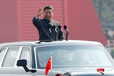 Chinese President Xi Jinping waves from the sunroof of a car as he addresses a military parade in China.