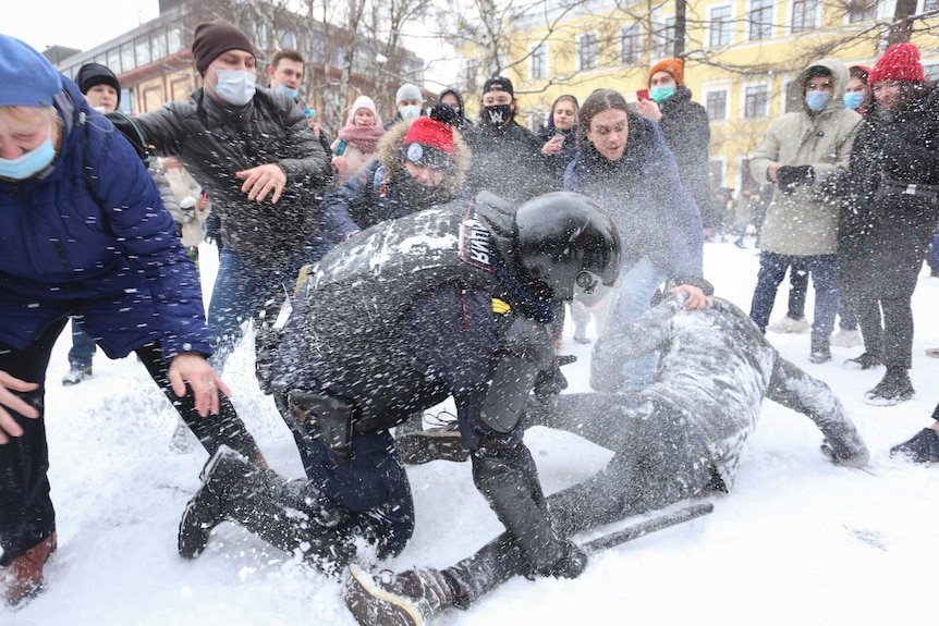 A policeman detains a protesters who is on the ground in the snow, while protesters try to help him.
