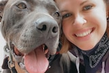 A young woman smiles as she poses for a selfie with a large grey dog with it's tongue hanging out.