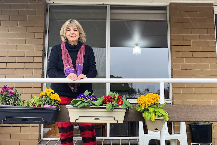 a woman sitting on her balcony alone