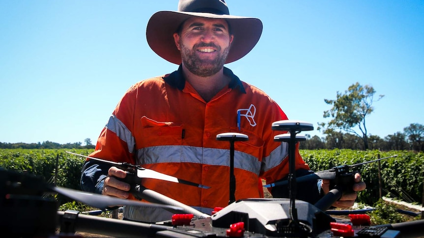 Drone pilot Luke Jurgens looks at the camera, he is wearing a big hat and high visibility shirt, standing with his drone.