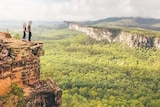 A photo of a couple standing on the edge of a sandstone cliff posted on instagram