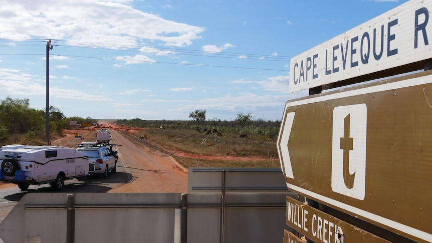 Image of caravans pulling onto a road, with a road sign in the immediate foreground.