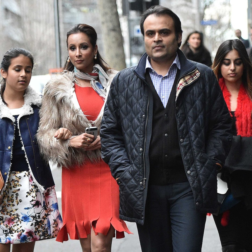 Panjak and Radhika Oswal walk along the footpath towards a camera with their two daughters.
