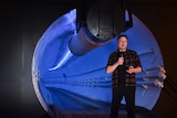 Elon Musk wears a plaid shirt, black t-shirt and black trousers as he speaks at the mouth of a blue-lit tunnel with microphone.