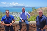 Three men wearing blue shirts smiling at the camera. In the background is an aerial view of Magnetic Island and Townsville.