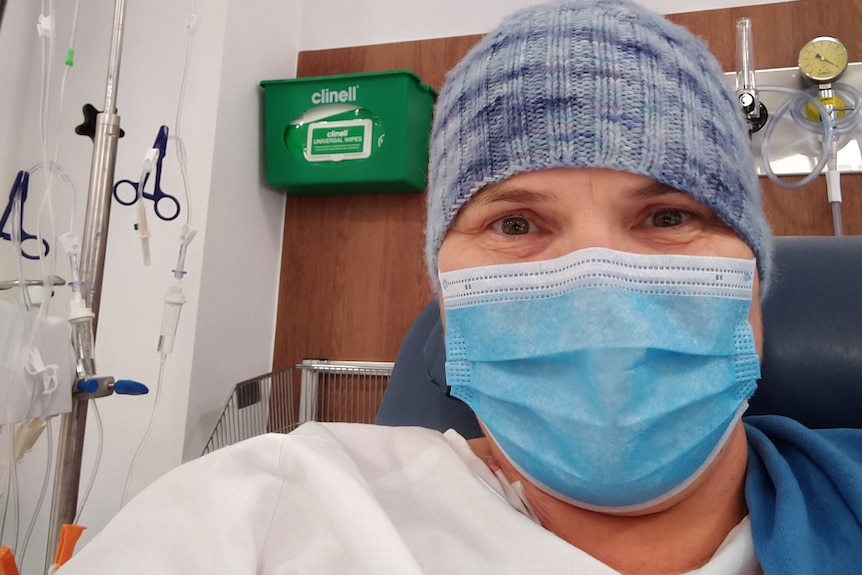 A woman wearing a blue face mask and a beanie in a hospital.