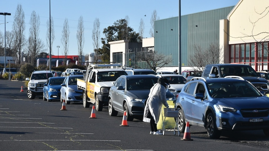 A row of cars at a drive-through testing clinic.