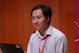 """Scientist He Jiankui stands behind a podium with """"SECOND INTERNATIONAL SUMMIT ON HUMAN GENOME EDITING"""" written on it."""
