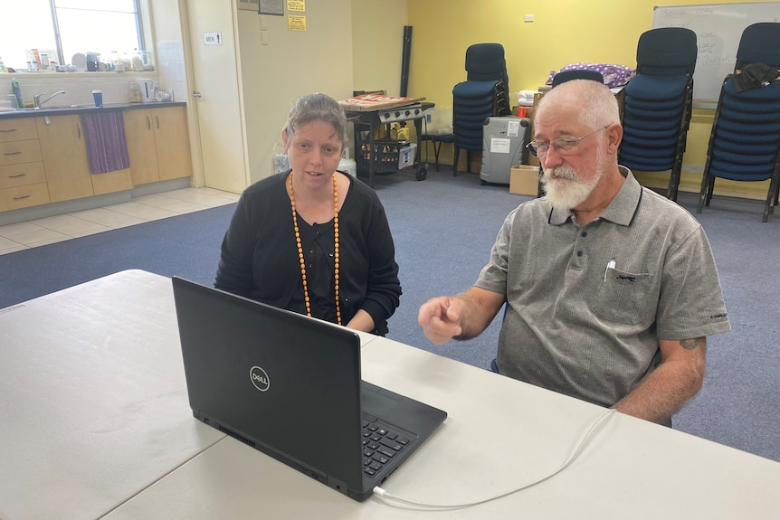 A young woman sits beside an older, bearded man at a laptop