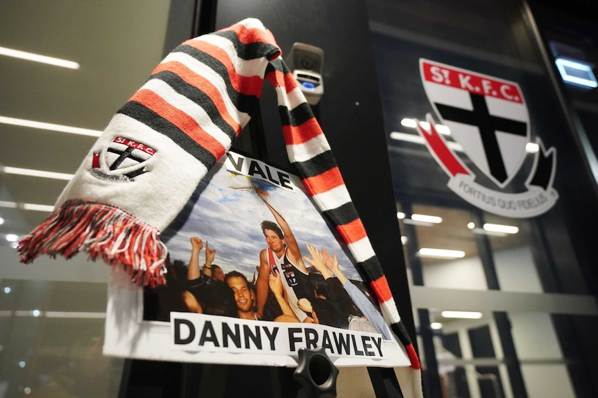 """A picture with the words """"Vale Danny Frawley"""" is placed on a door with a St Kilda scarf on it."""
