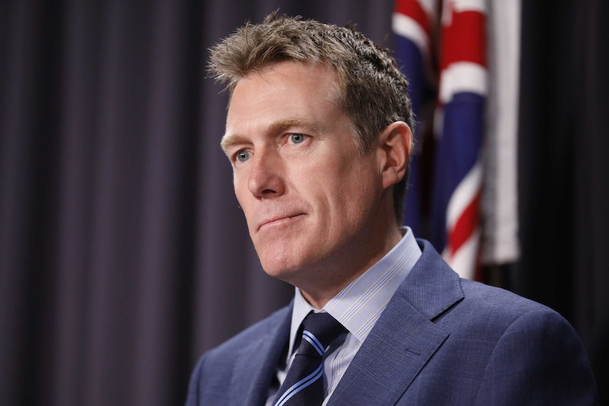 Christian Porter stands in front of an Australian flag