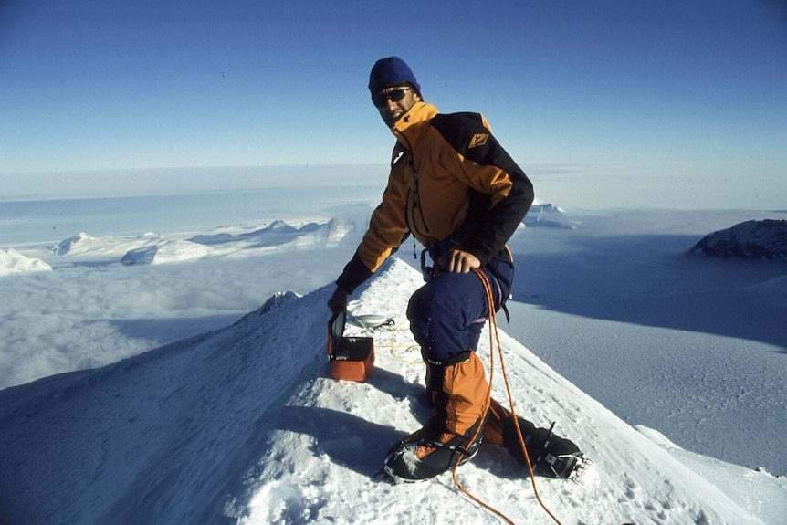 At the top of one of a series of huge, snow-capped mountains, Damien Gildea, in snow clothes, beanie and sunglasses, smiles.