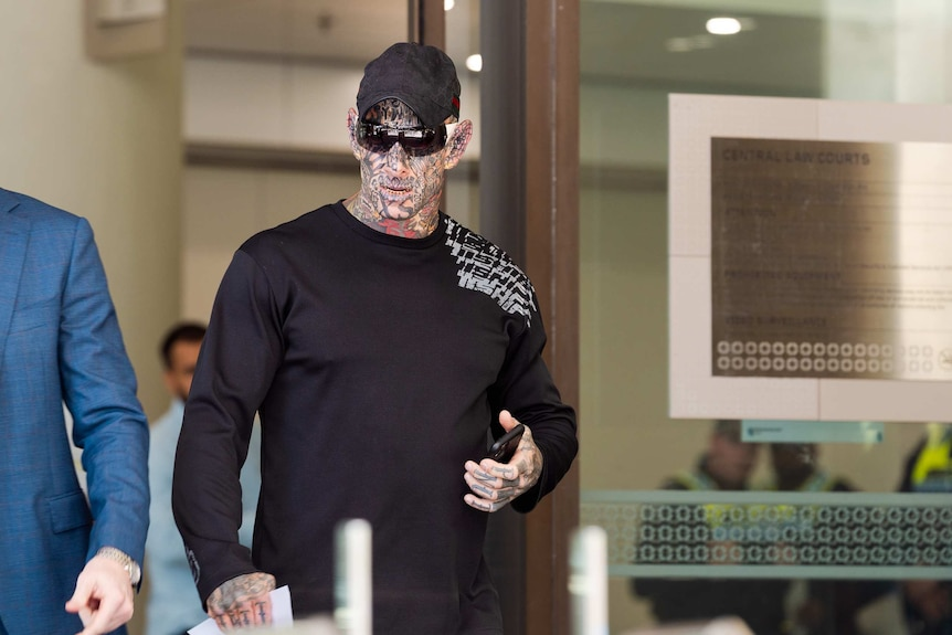 Brajkovich holds a mobile phone as he walks out of court. He has tattoos covering his face, neck and hands.