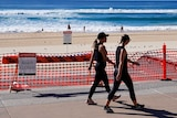 Two women in exercise gear walk past a sign blocking access to a beach. People can still be seen swimming