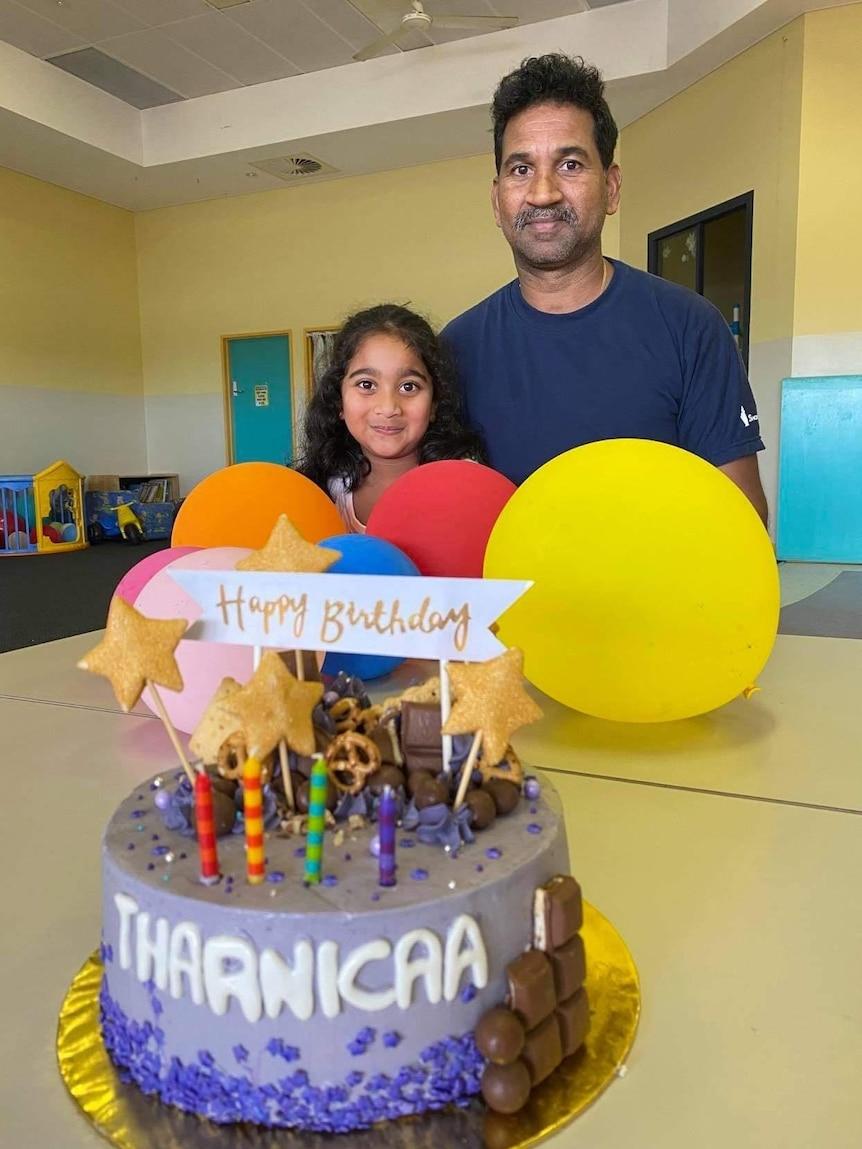 Kopica Murugappan and Nades Murugappan sit by a table with balloons and a birthday cake