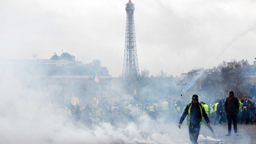 Gilets Jaunes protesters walk through tear gas smoke on Champs Elysees with Eiffel Tower in background