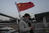 Residents taking the ferry stands near a Chinese national flag in Wuhan