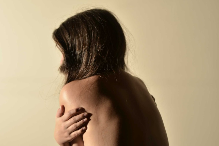 A woman sitting up in bed with no top on hugging herself tightly